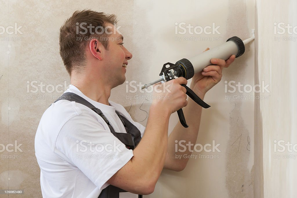 Worker grouts with silicone royalty-free stock photo