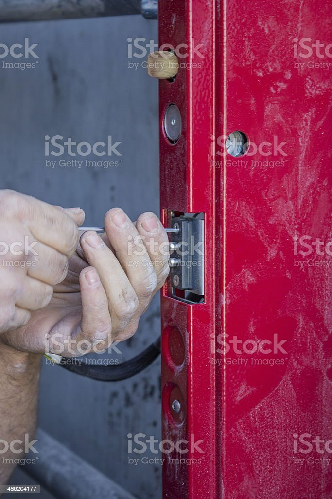 worker hands adjusting mechanism of lift door stock photo