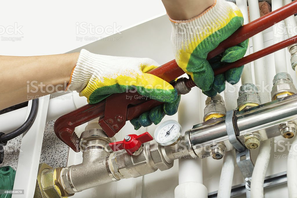 Worker hands fixing heating system stock photo