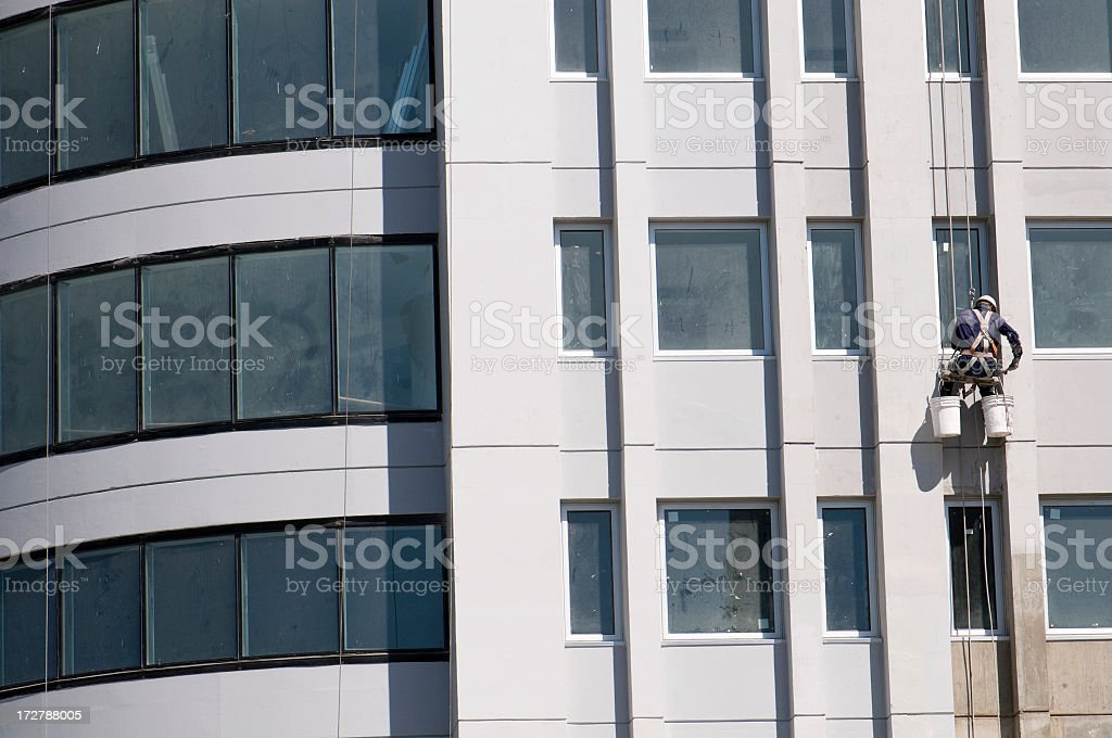 A worker hanging on ropes on the outside of a new building royalty-free stock photo