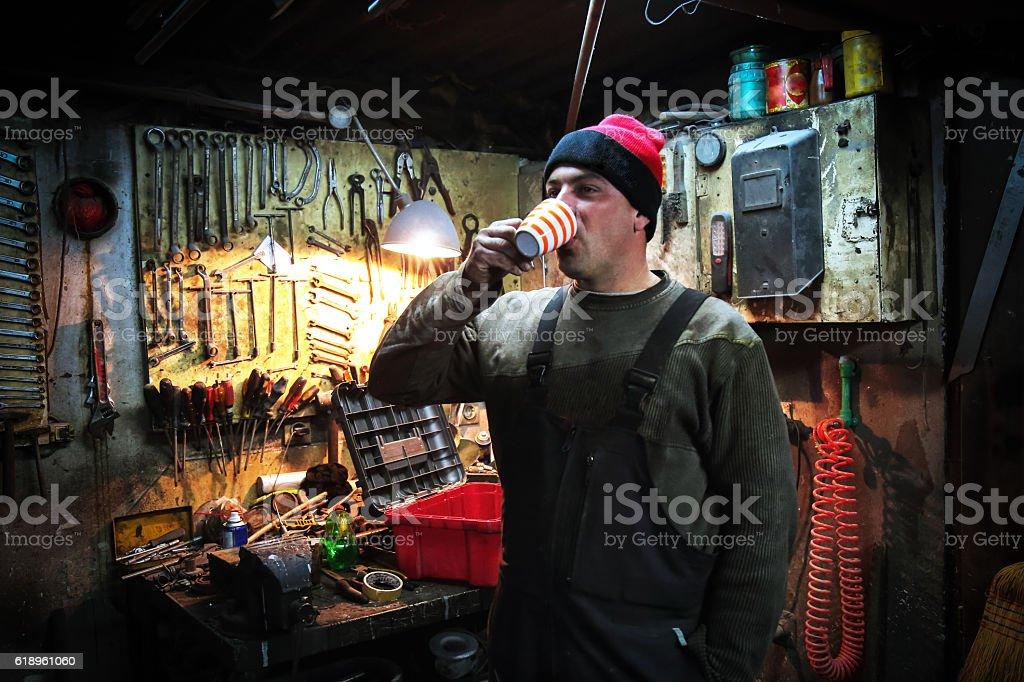 Worker having a coffee break at Vintage Auto Repair Shop. stock photo