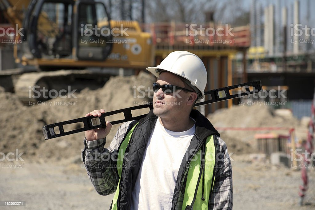 Worker holding a level - horizontal royalty-free stock photo