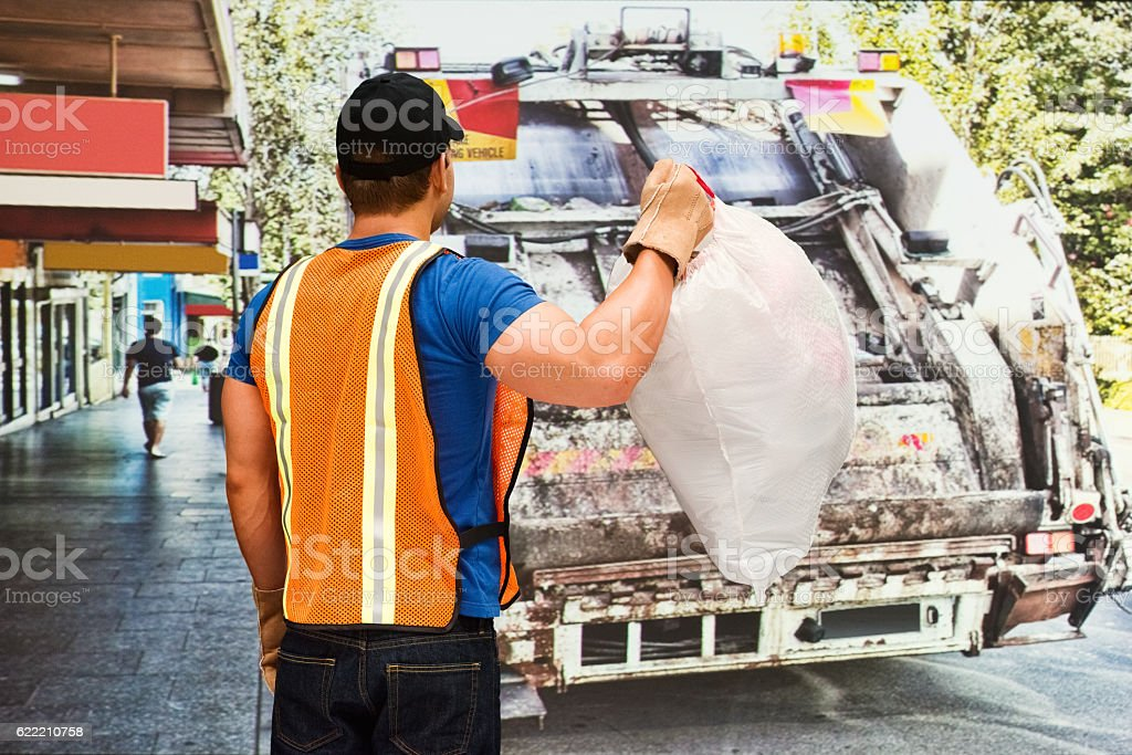 Worker holding garbage bag outdoors stock photo