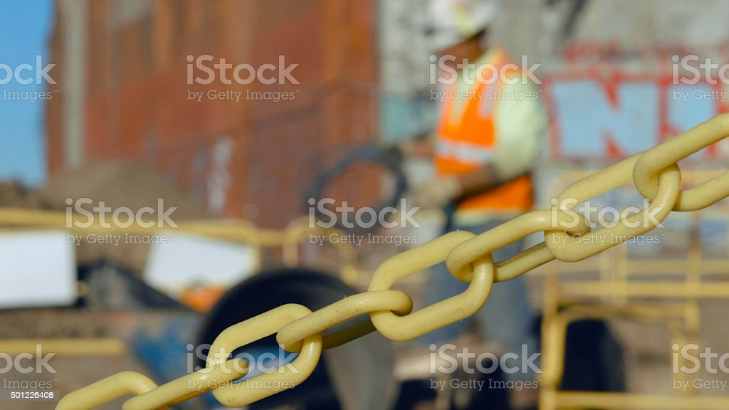 Worker holding hank of metal cable on construction site stock photo