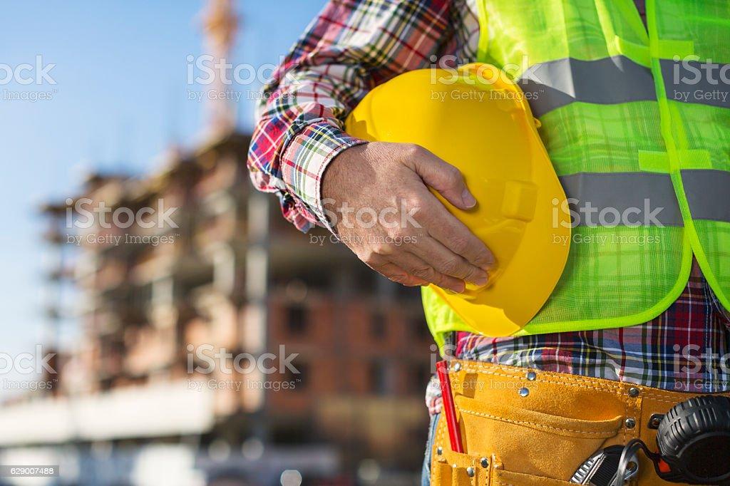 Worker holding hard hat close up shot stock photo