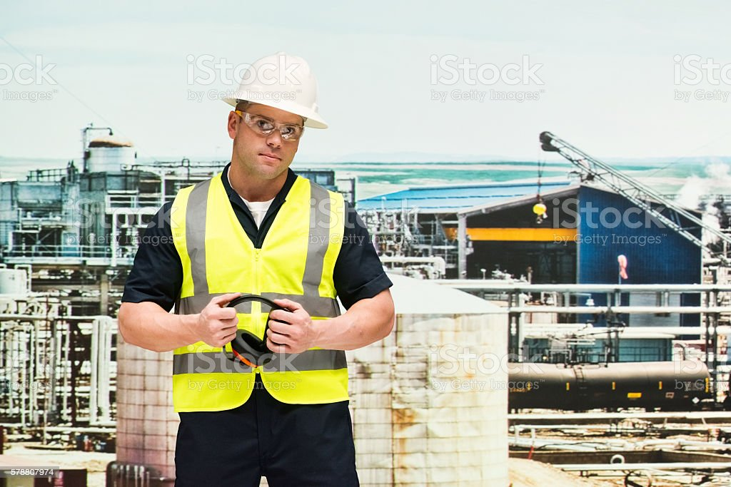 Worker holding headphone in front of oil industry stock photo