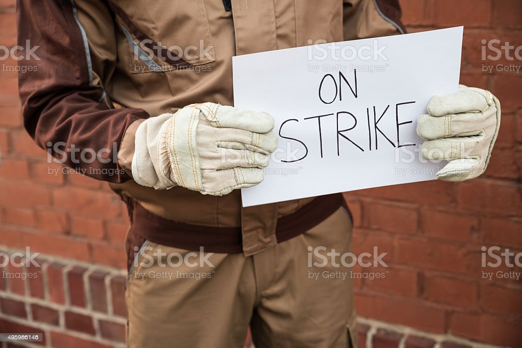 Worker Holding Placard With The Text On Strike stock photo