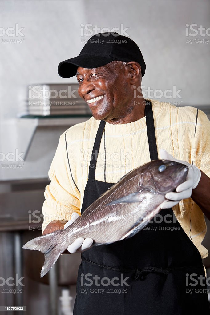 Worker holding seabass in fish market stock photo