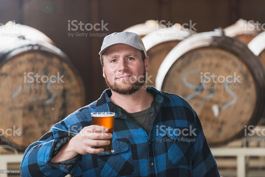 Worker in a microbrewery holding glass of beer stock photo