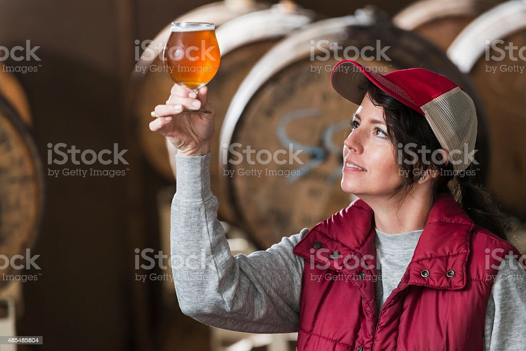 Worker in a microbrewery inspecting glass of beer stock photo