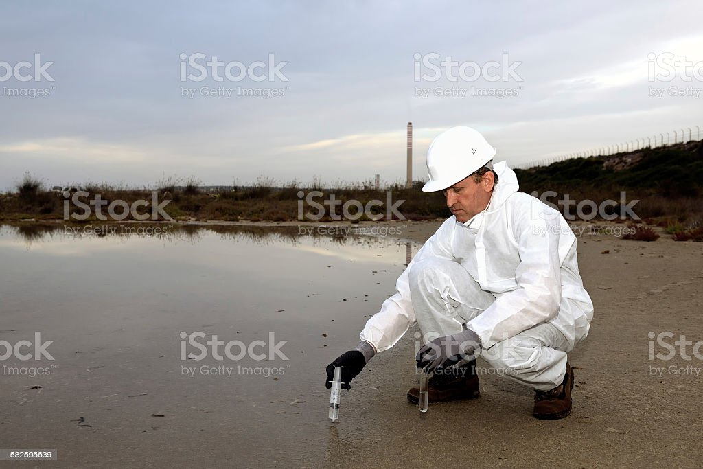 Worker in a protective suit examining pollution stock photo