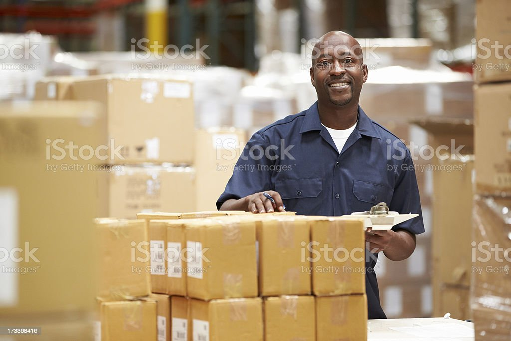 A worker in a warehouse preparing goods for delivery stock photo