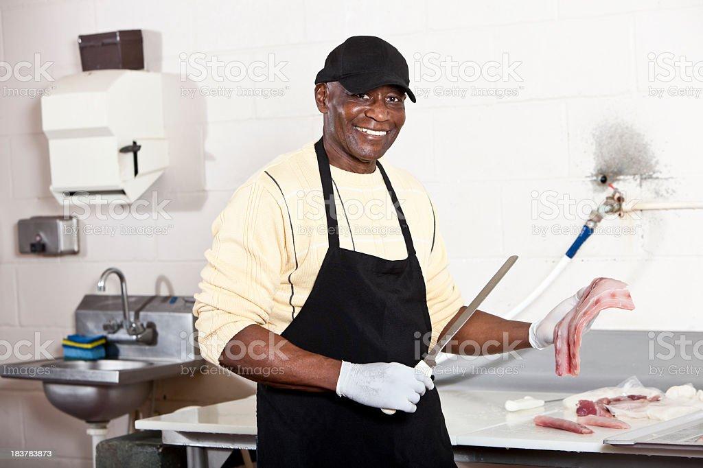 Worker in back room of fish market holding fillet knife stock photo