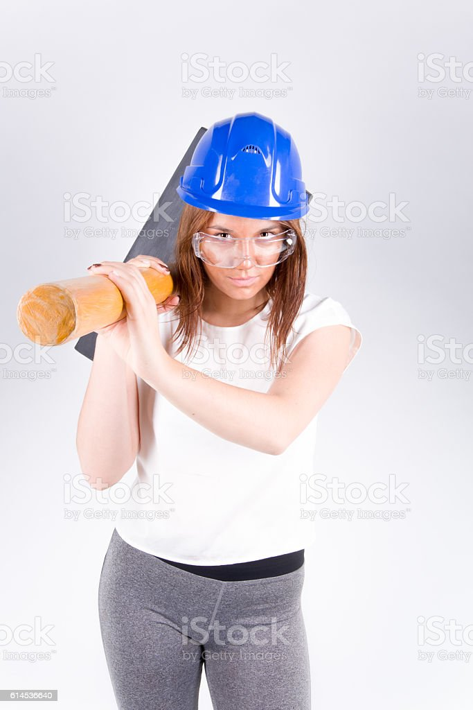 Worker in blue helmet female with a sledgehammer stock photo