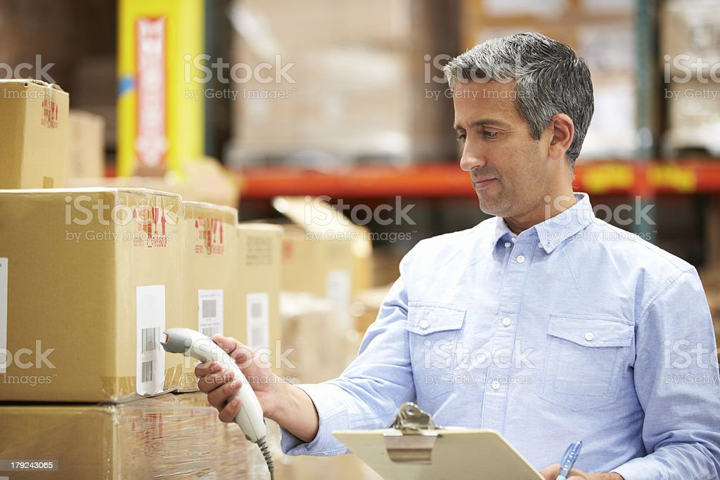 Worker in blue shirt scanning packages in a warehouse stock photo