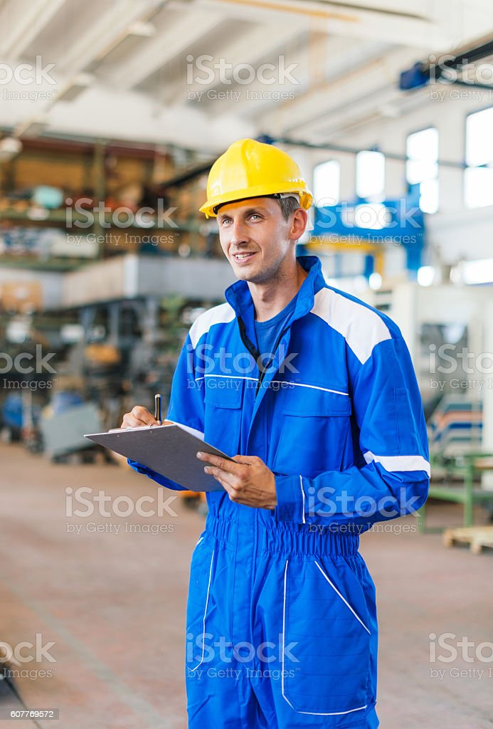 Worker in blue uniform with hardhat signing documents in warehouse stock photo