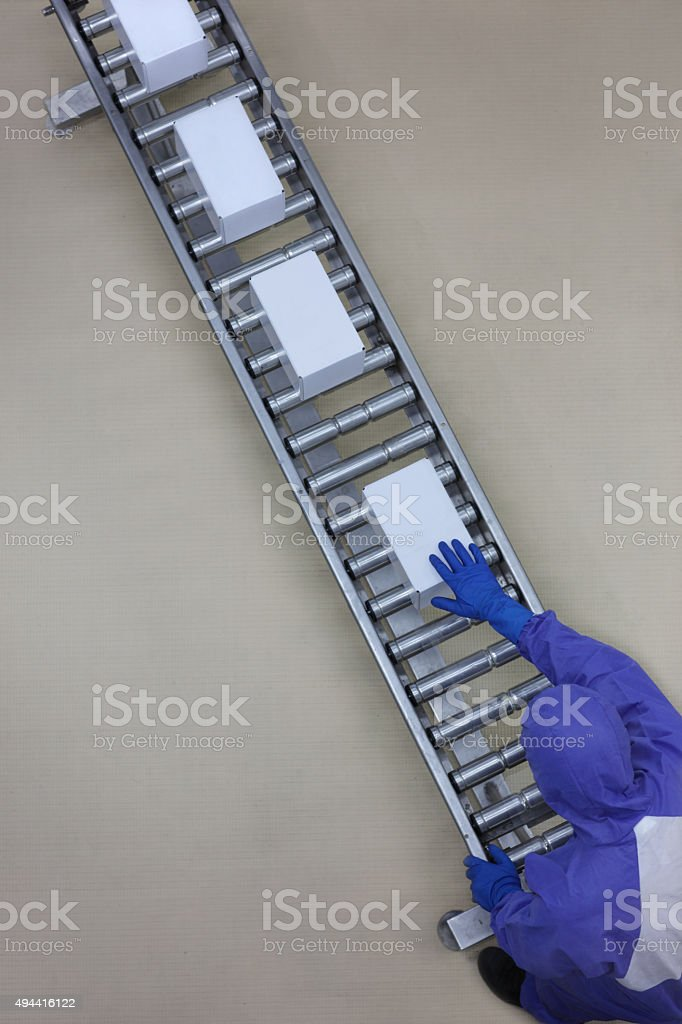 worker in blue uniform working with boxes on packing line stock photo