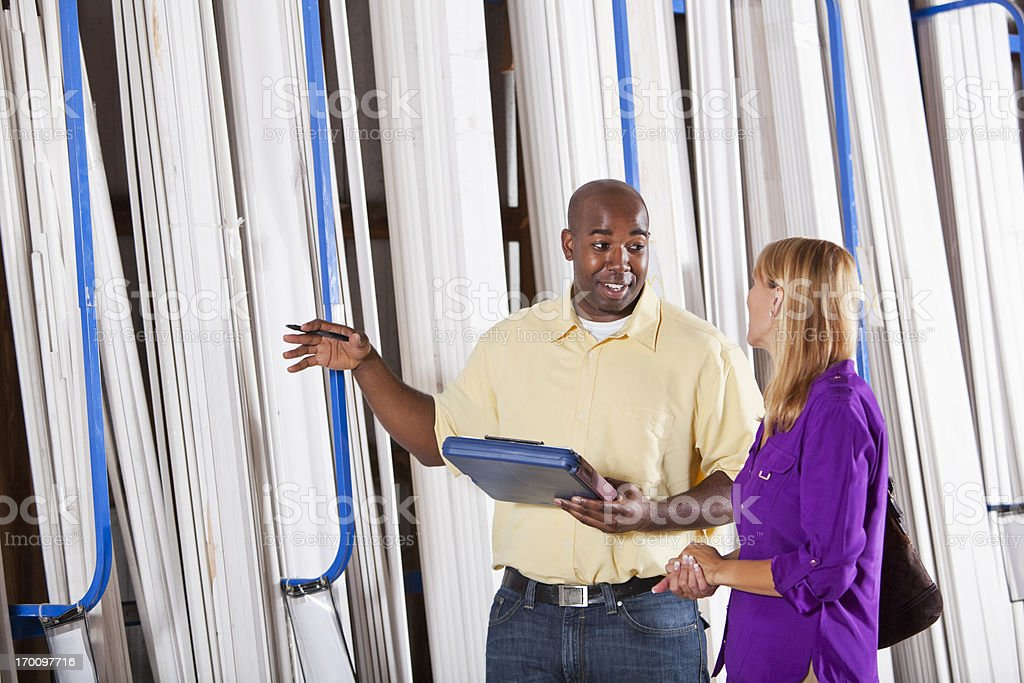 Worker in building supply store helping customer royalty-free stock photo