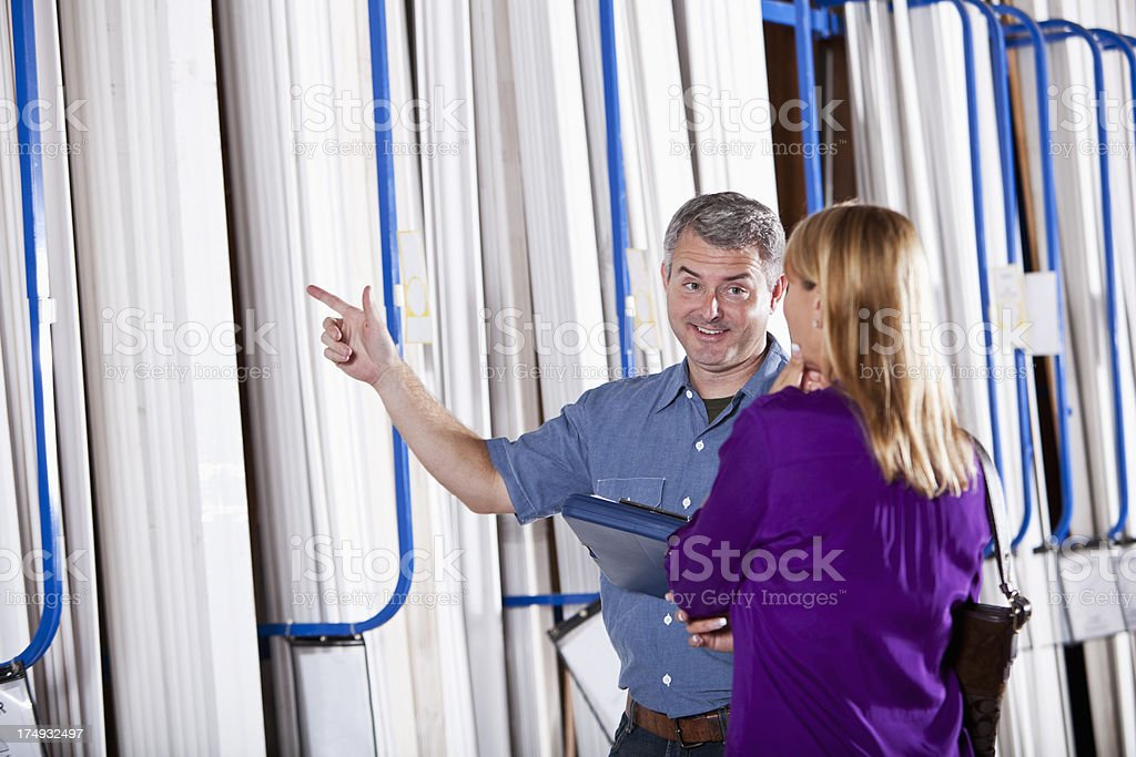 Worker in building supply store helping customer stock photo