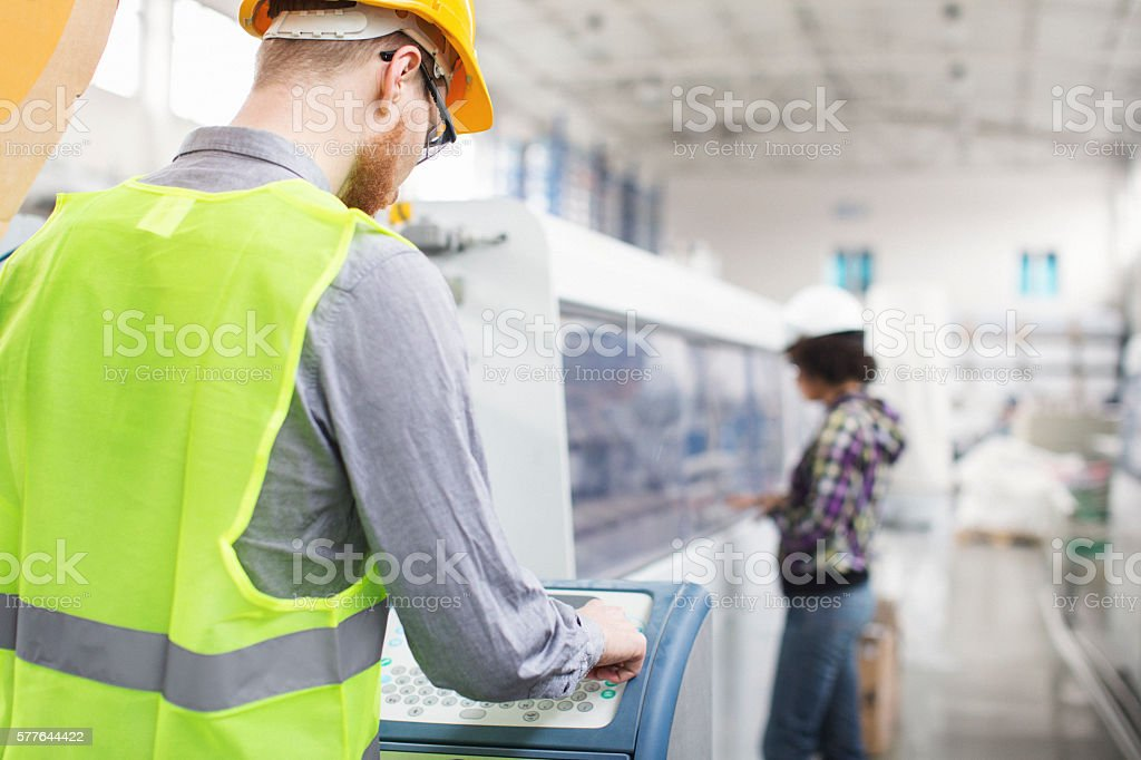 Worker in factory operating a machine stock photo