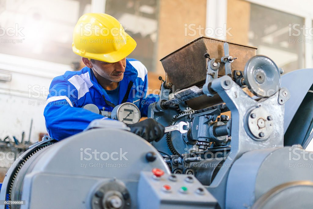 Worker in factory repairing hydraulic press and roll bars stock photo