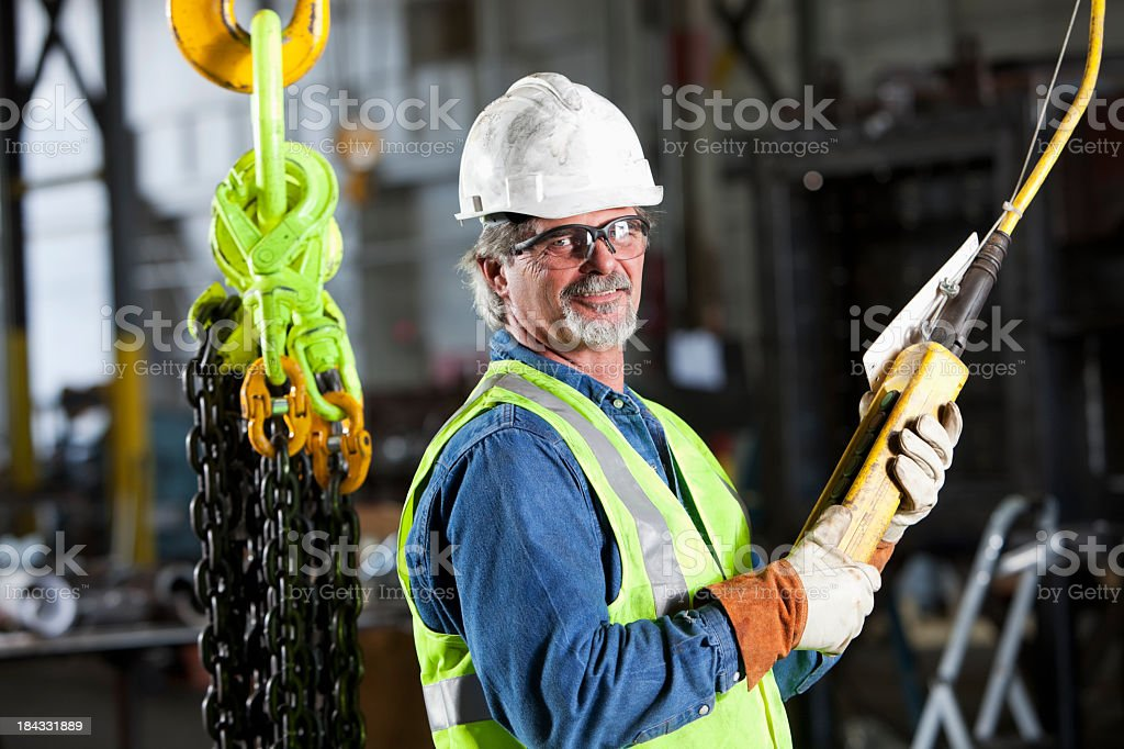 Worker in factory with industrial hook and chains royalty-free stock photo