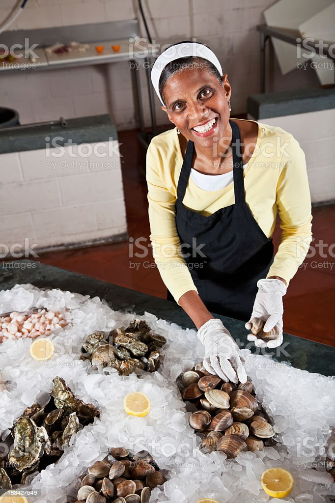 Worker in fish market arranging shellfish display royalty-free stock photo