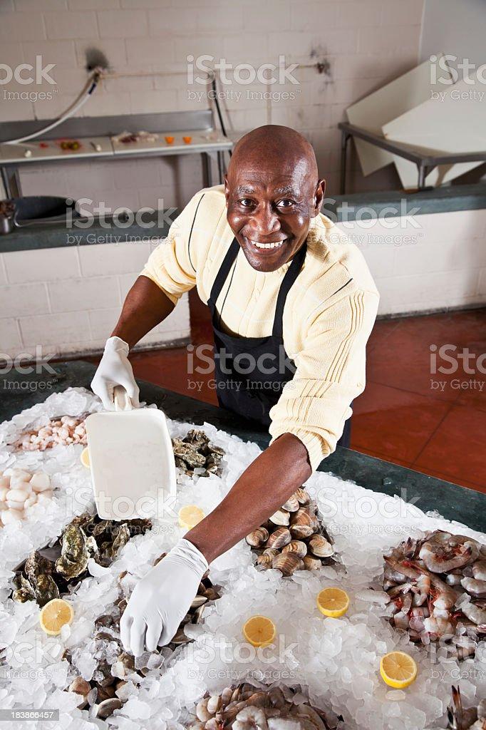 Worker in fish market arranging shellfish display stock photo
