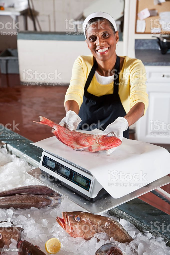 Worker in fish market holding red snapper stock photo