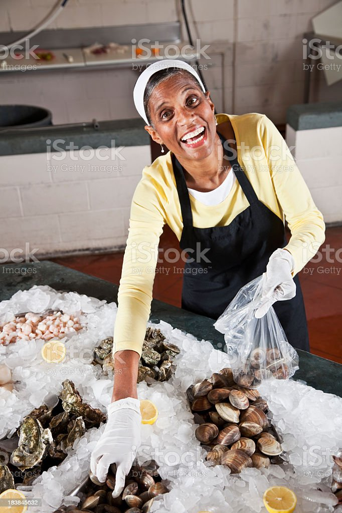 Worker in fish market putting clams into bag stock photo