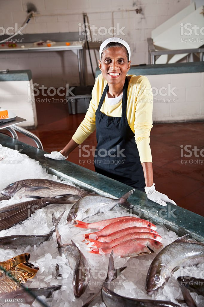 Worker in fish market with display of fresh catch stock photo
