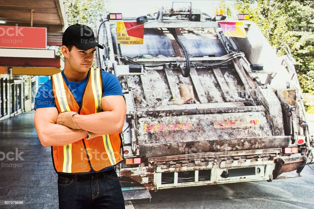 Worker in front of garbage can stock photo