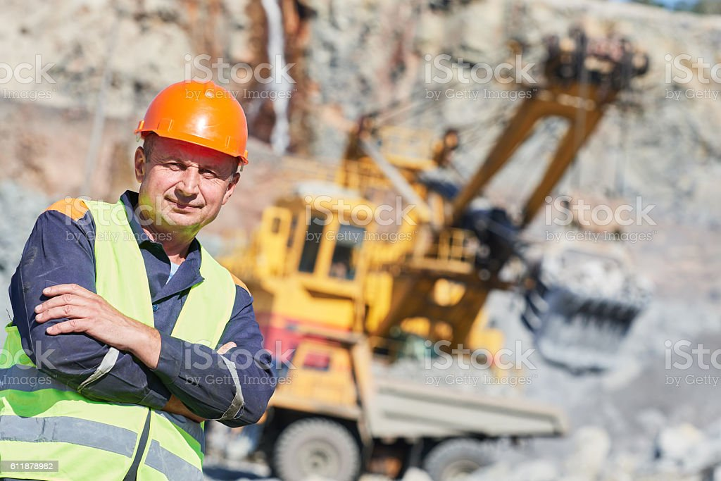 worker in front of heavy excavator and dumper truck stock photo