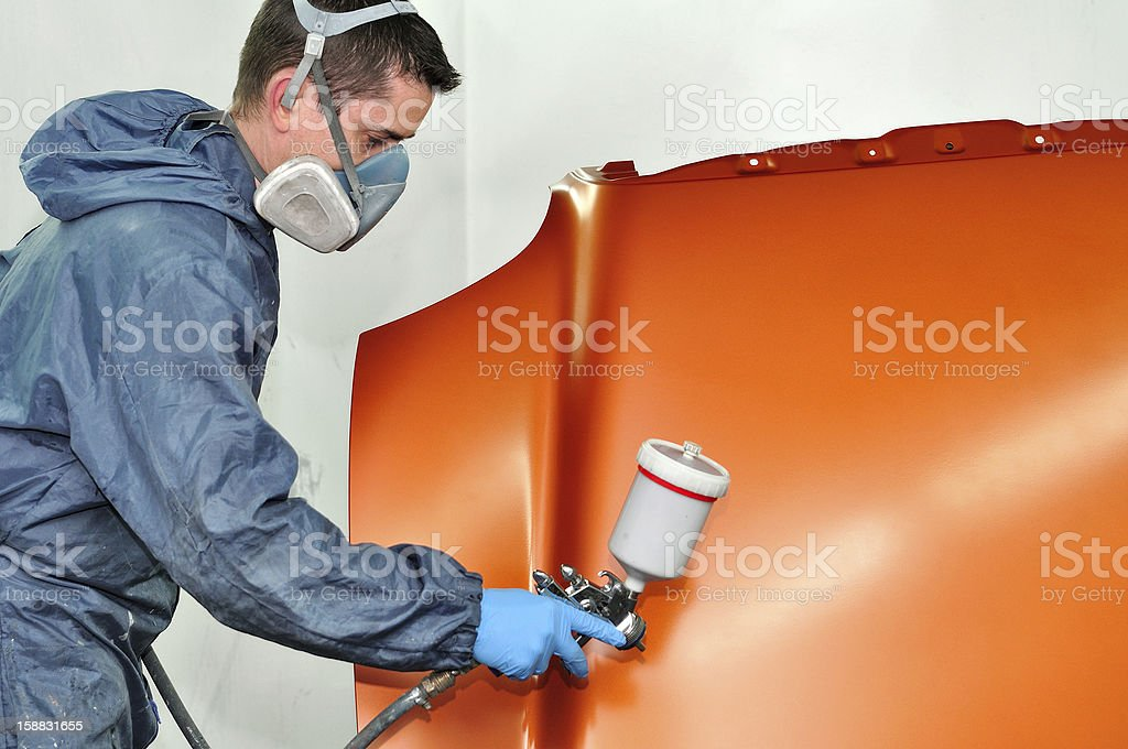 Worker in full suit painting a car hood orange stock photo