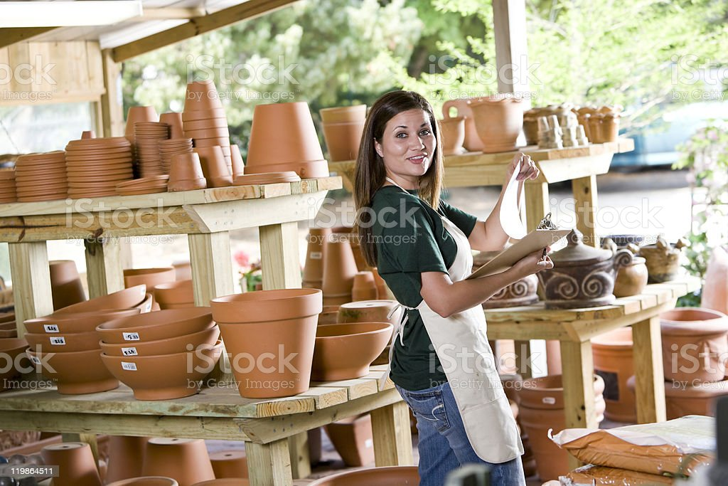 Worker in garden center store selling clay pots stock photo