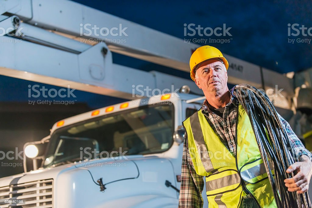 Worker in hardhat and safety vest outside truck stock photo