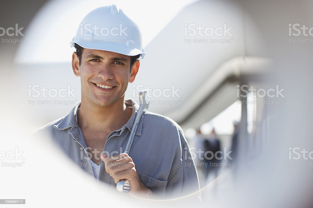 Worker in hard-hat holding wrench outdoors royalty-free stock photo