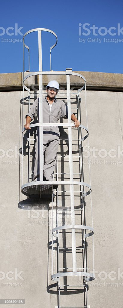 Worker in hard-hat standing on outdoor ladder royalty-free stock photo