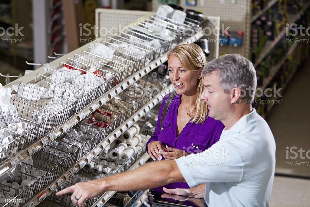 Worker in hardware store helping customer stock photo