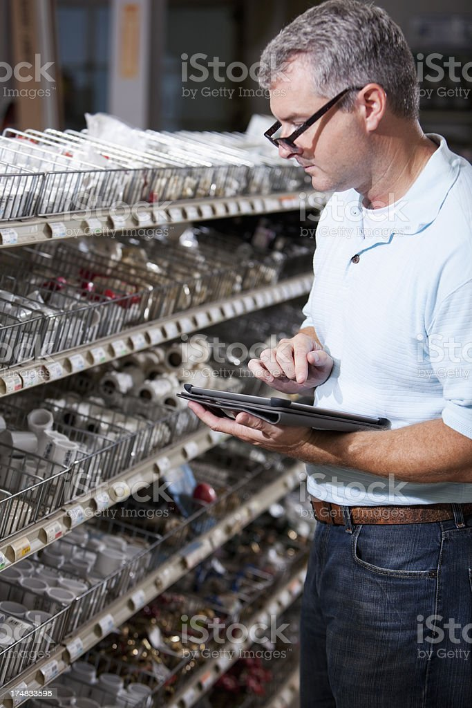 Worker in hardware store taking inventory stock photo