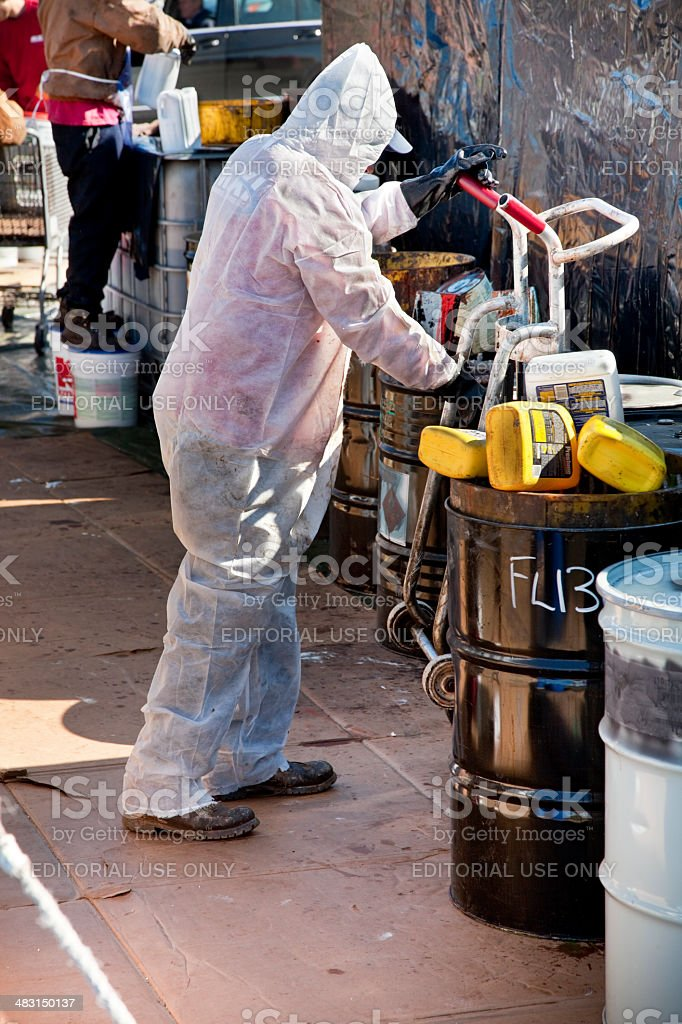 Worker in hazmat suit moving drum at Hazardous Waste collection stock photo