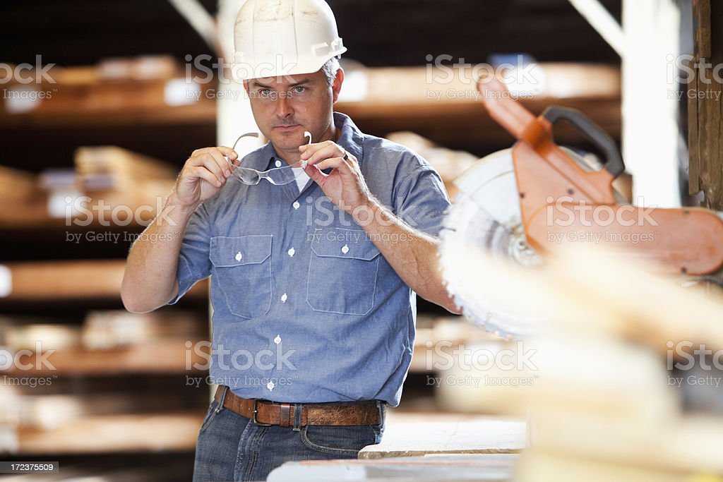 Worker in lumber aisle of building supply store stock photo