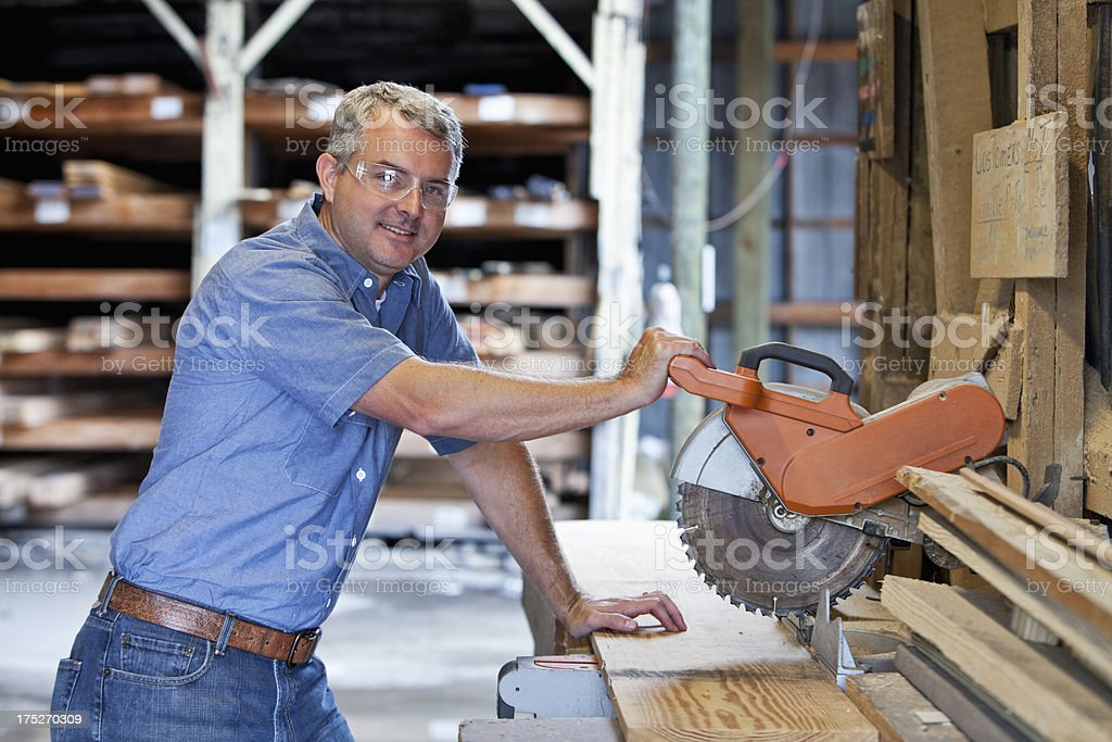 Worker in lumberyard sawing wood plank stock photo