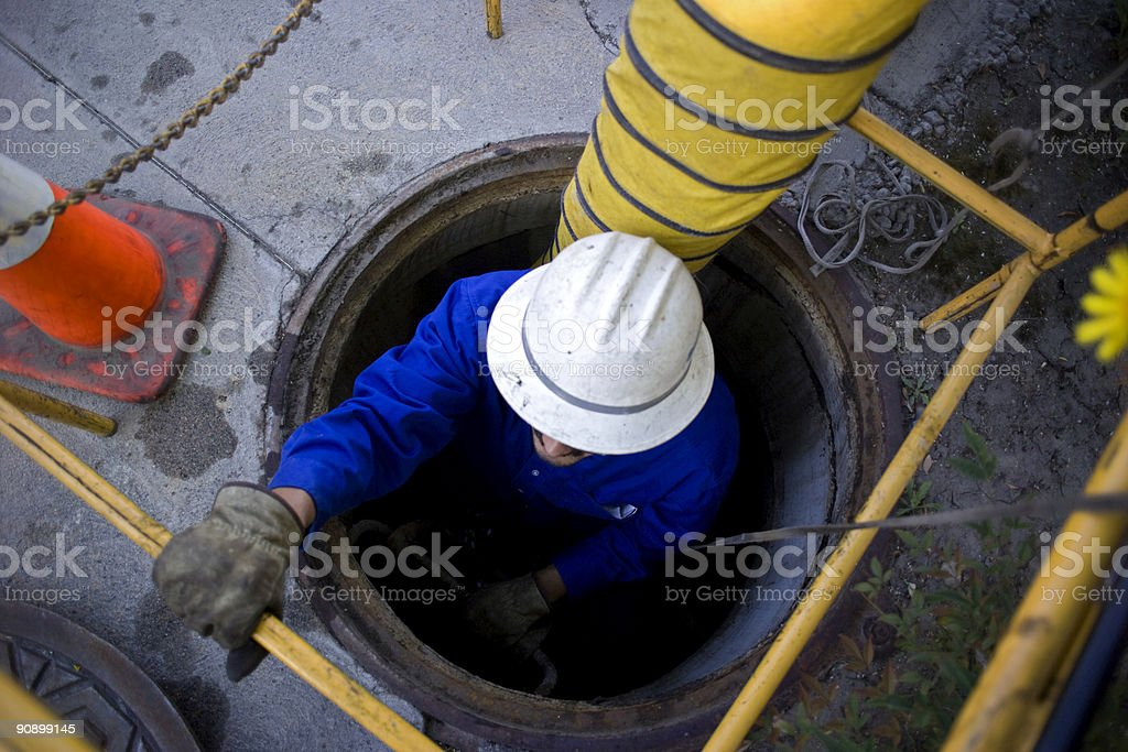 Worker in man hole stock photo