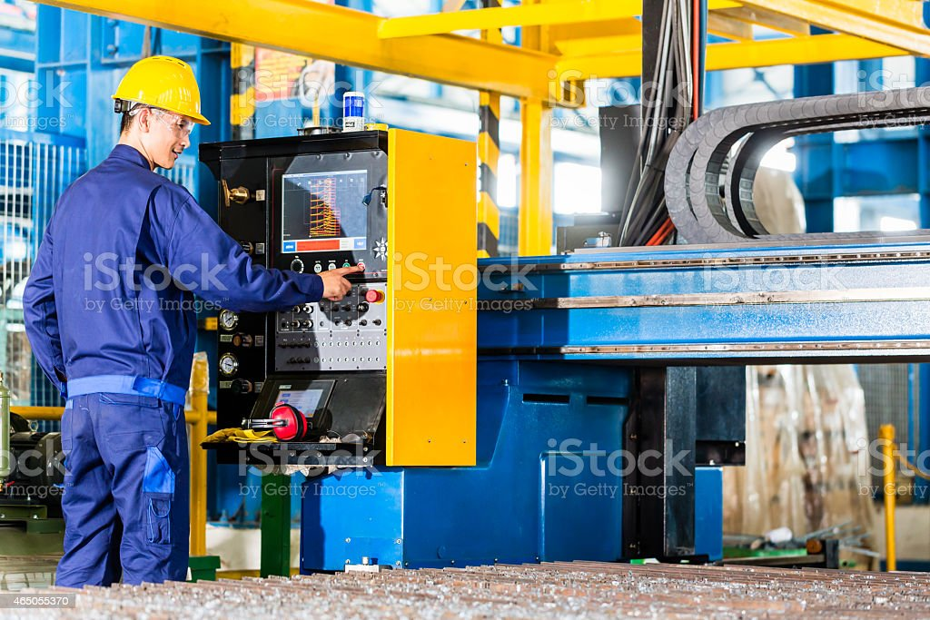 Worker in manufacturing plant at machine control panel stock photo