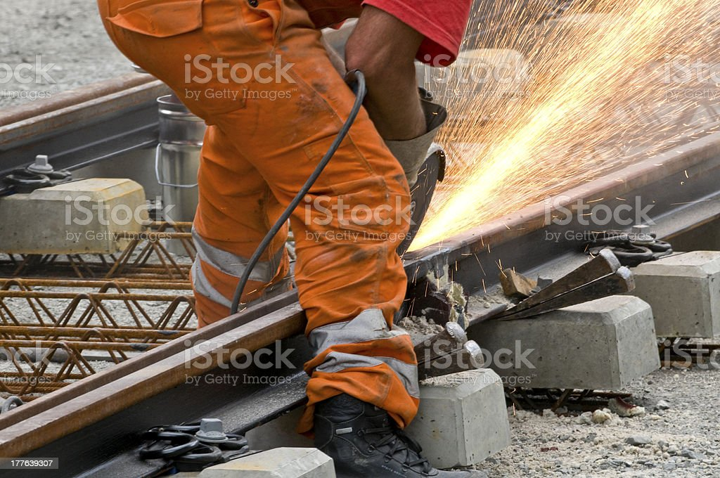A worker in orange suit welding a section of a railway track royalty-free stock photo