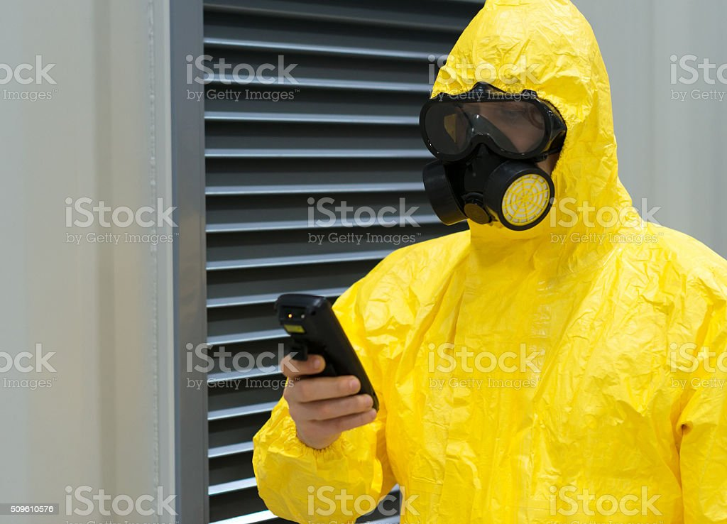 Worker in protective chemical suit checking radiation with geiger counter. stock photo