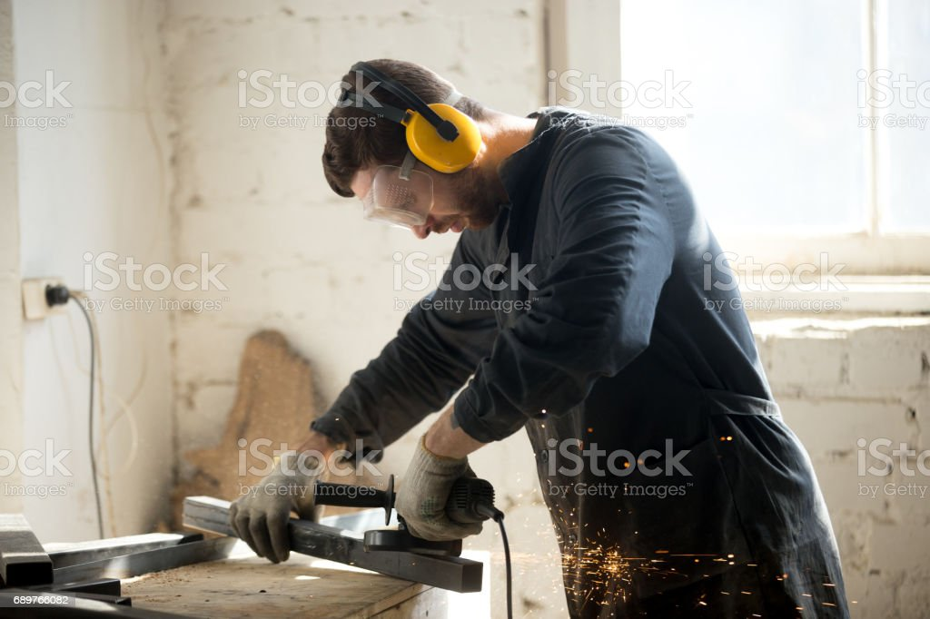 Worker in protective clothes working in workshop stock photo