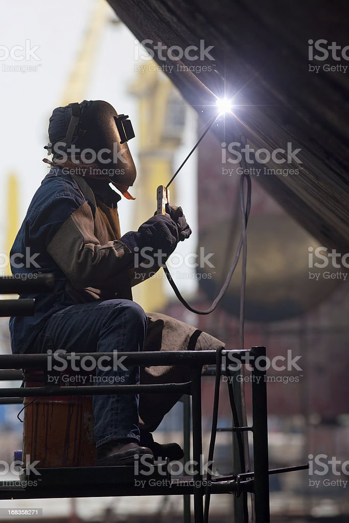 Worker in protective gear welding new plates on ship's hull. royalty-free stock photo
