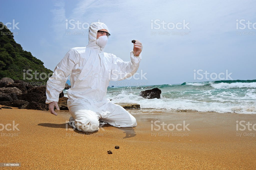 Worker in protective suit examining pollution at a beach royalty-free stock photo